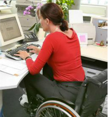 business woman in wheelchair at desk typing on a computer