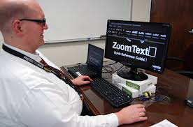 Photo of an employee working at desk using zoom text which is visible on a computer screen